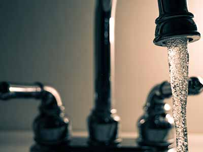 close up photo of a running tap with water pouring out