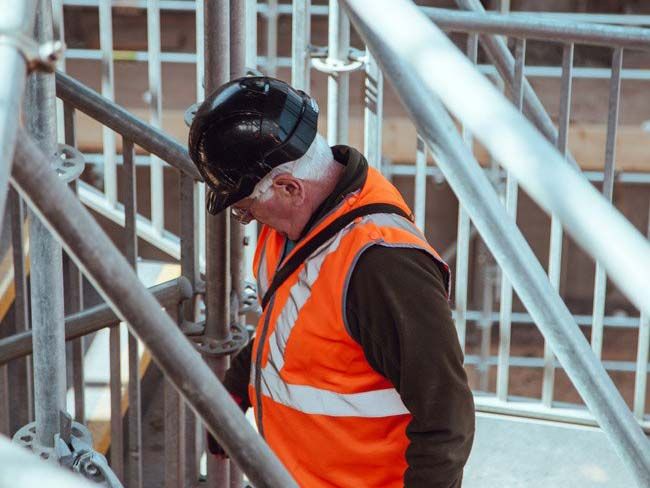 Man in hard hat and orange safety vest looking down