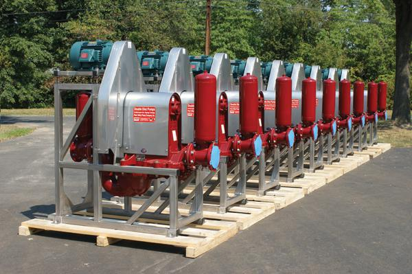a row of large new red and silver pumps sitting on pallets outside
